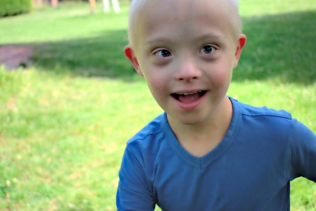 Junge mit einem down-syndrom, das in einem park spielt Premium Fotos