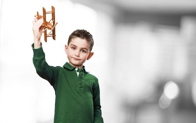 Junge mit einer holz-flugzeug spielen Kostenlose Fotos