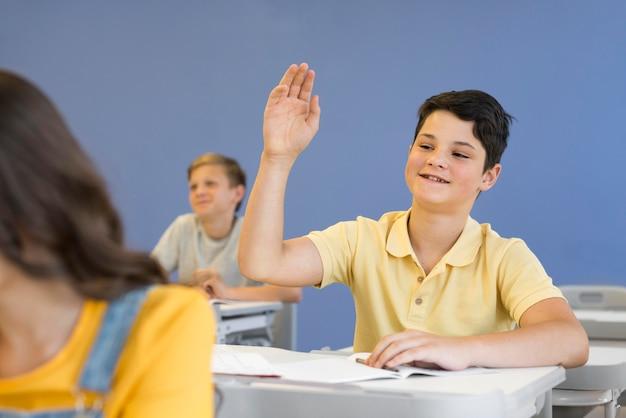 Junge mit erhobener hand Kostenlose Fotos