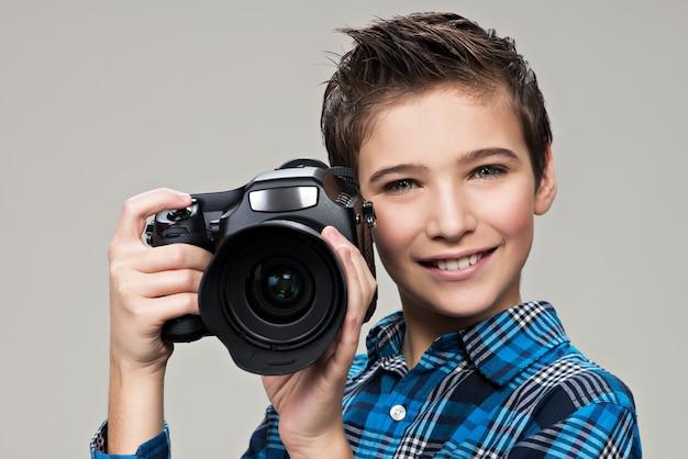 Junge mit fotokamera, die bilder macht. porträt des kaukasischen jungen mit der digitalkamera in den händen Kostenlose Fotos