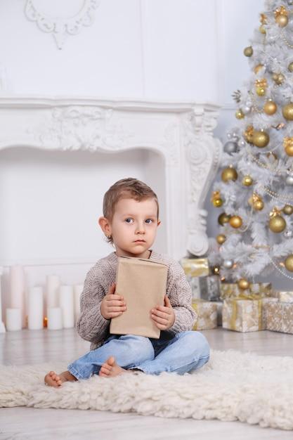 Junge mit geschenken unter dem weihnachtsbaum Premium Fotos