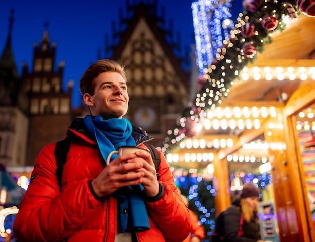 Junge mit getränk auf weihnachtsmarkt in breslau, polen Premium Fotos