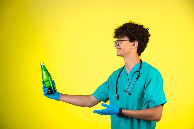 Junge mit lockigem haar in medizinischer uniform und handmasken, die auf eine flasche flüssigkeit schauen und lächeln. Kostenlose Fotos