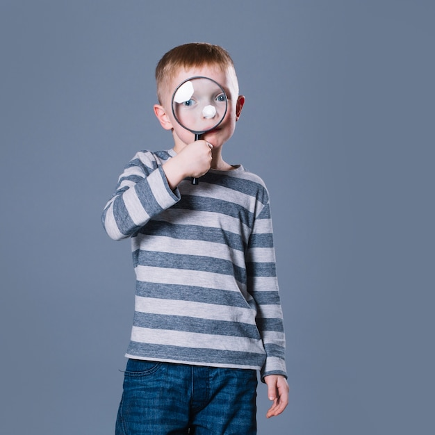 Junge mit lupe Kostenlose Fotos
