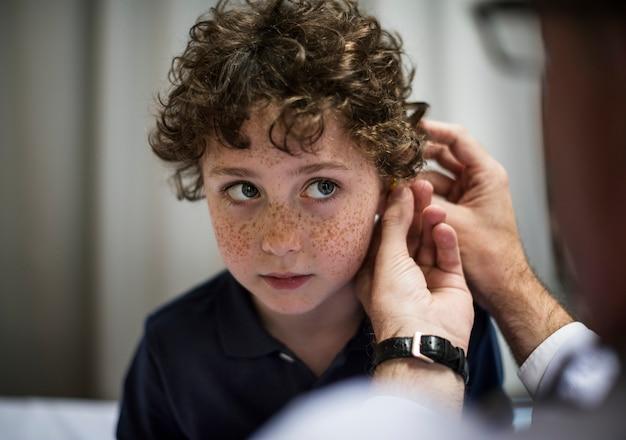 Junge mit seinen ohren überprüft Premium Fotos