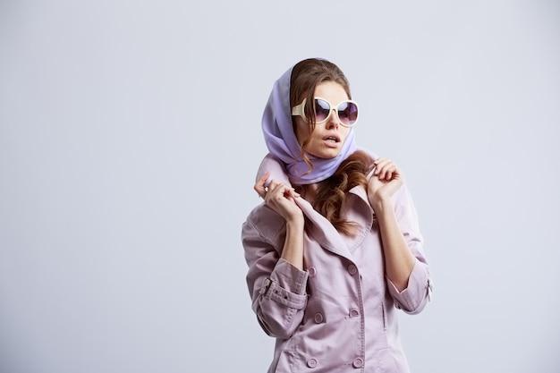 Junge modefrau, die im studio trägt rosa mantel und weiße sonnenbrille aufwirft Premium Fotos