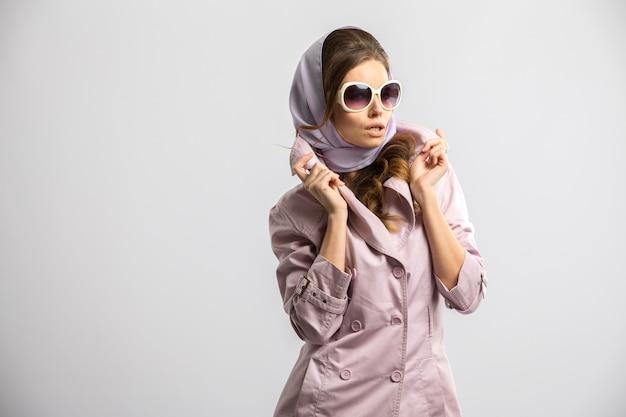 Junge modefrau, die rosa mantel und weiße sonnenbrille tragend aufwirft Premium Fotos