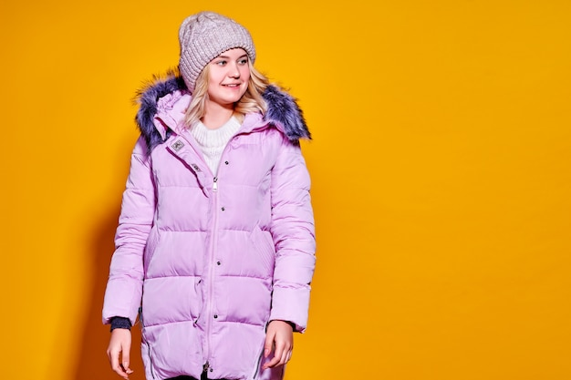Junge modefrau in der kurzen violetten daunenjacke Premium Fotos