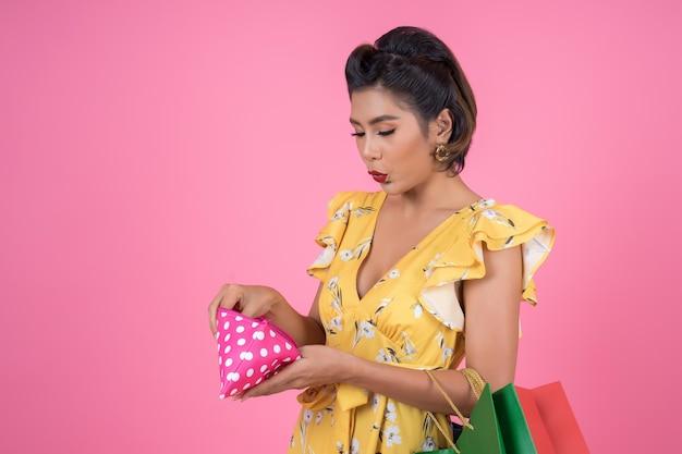 Junge modefrauenhand, die geldbörse und einkaufstaschen hält Kostenlose Fotos