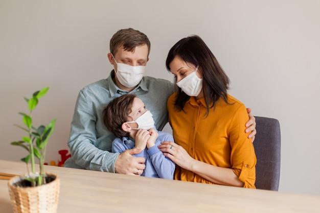 Junge moderne coronavirus-familie unter quarantäne in medizinischen masken. der ruf, zu hause zu bleiben, stoppt die pandemie. selbstisolation zusammen ist die lösung. pflege covid-19. mama papa sohn millennials Premium Fotos