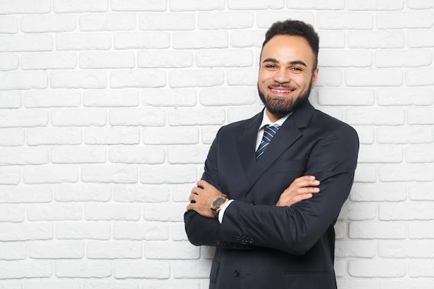 Junge moderne männer in einer klage gegen backsteinmauer Premium Fotos