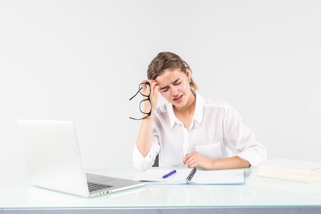 Junge müde frau vor einem laptop am schreibtisch, lokalisiert auf weißem hintergrund Kostenlose Fotos