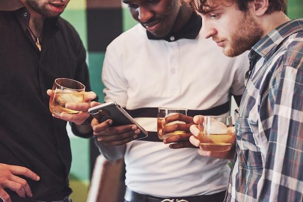 Junge multiethnische leute feiern und trinken whisky toast Premium Fotos