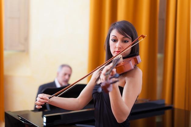 Junge musikerfrau, die ihre violine spielt Premium Fotos