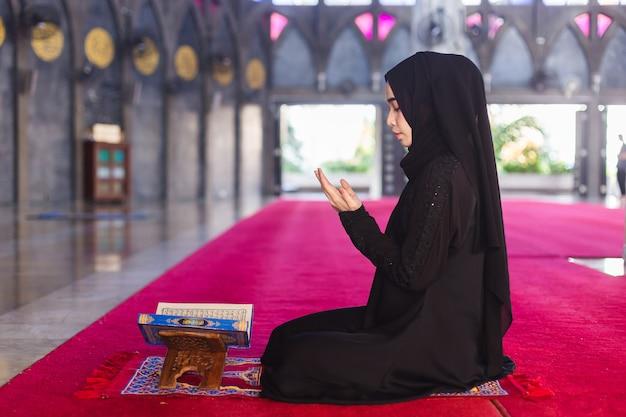 Junge muslimische frau im schwarzen kleid des korans las koran und wünschte, in der moschee zu beten. machen sie einen wunsch und lesen sie den koran im ramadan. Premium Fotos