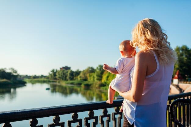 Junge mutter, die baby hält und flusslandschaft zeigt. Premium Fotos