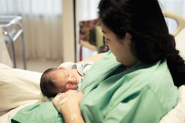 Junge mutter, die ihr neugeborenes baby hält, das erste lebenstage am krankenhaus schläft. Premium Fotos