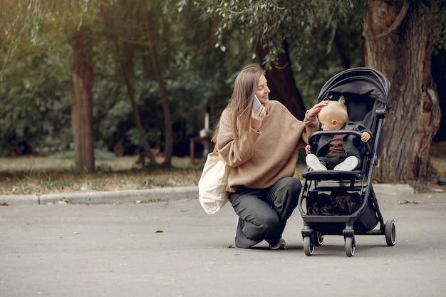 Junge mutter, die in einen herbstpark mit wagen geht Kostenlose Fotos