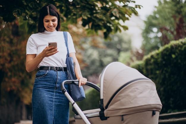 Junge mutter, die mit kinderwagen im park geht und am telefon spricht Kostenlose Fotos