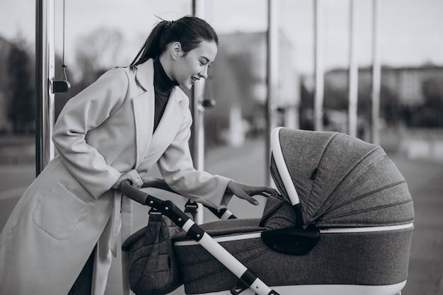 Junge mutter, die mit kinderwagen im park geht Kostenlose Fotos