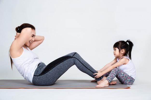 Junge mutter, die reizende tochter mit gymnastischem ausbildet Kostenlose Fotos