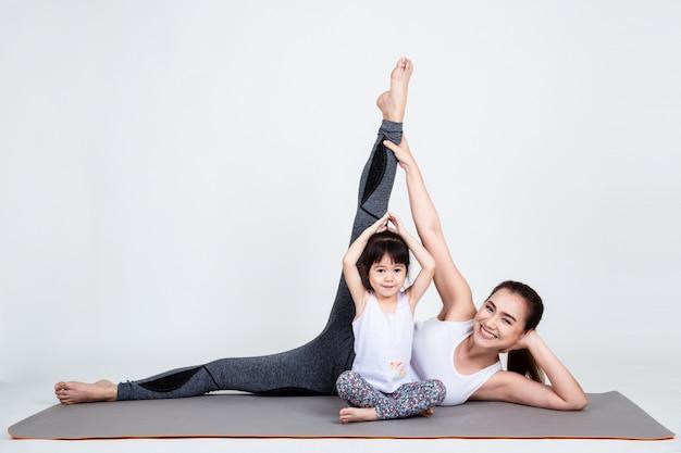 Junge mutter, die reizende tochter mit yoga ausbildet Kostenlose Fotos