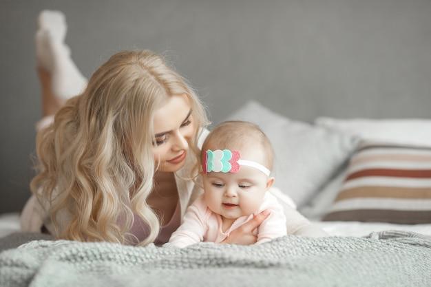 Junge mutter, die um ihrem kleinen baby sich kümmert. schöne mutter und ihre tochter drinnen im schlafzimmer. liebevolle familie. attraktive mutter, die ihr kind hält. Premium Fotos