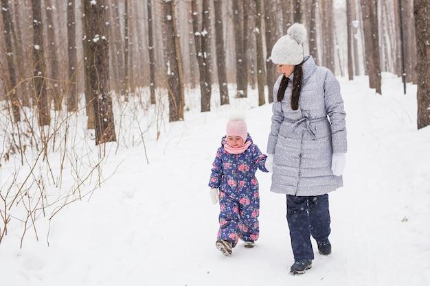 Junge mutter geht mit ihrer tochter im winterwald spazieren Premium Fotos