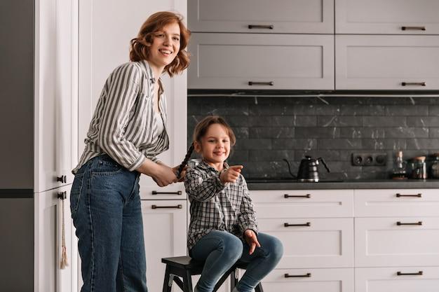 Junge mutter in hemd und jeans steht neben ihrer tochter, die auf stuhl sitzt. Kostenlose Fotos