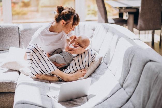 Junge mutter mit ihrem kind, das zu hause an einem computer arbeitet Kostenlose Fotos
