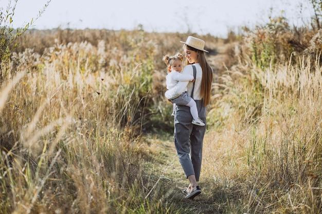 Junge mutter mit ihrer kleinen tochter auf einem herbstgebiet Kostenlose Fotos