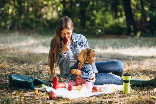 Junge mutter mit ihrer kleinen tochter in einem herbstpark, der picknick hat Kostenlose Fotos