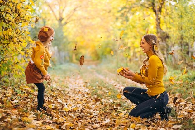 Junge mutter mit ihrer kleinen tochter in einem herbstpark Kostenlose Fotos
