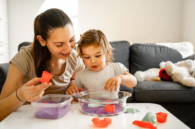 Junge mutter mit kind, das kinetischen sand spielt. fröhliche zeit miteinander. kreativitätsentwicklung Premium Fotos