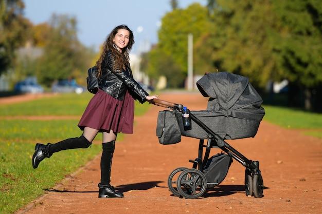 Junge mutter mit kinderwagen. familien-, kinder- und elternschaftskonzept - glückliche mutter geht mit einem kinderwagen in den park. Premium Fotos
