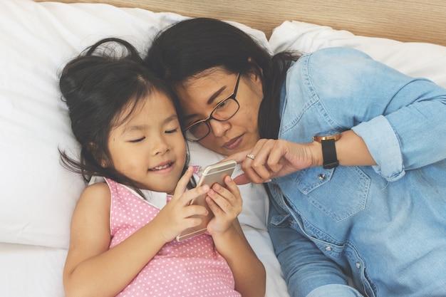 Junge mutter und ihre kleine tochter benutzen zu hause einen smartphone auf dem bett Premium Fotos