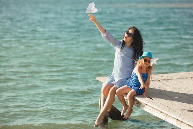 Junge mutter und ihre nette tochter an der seeseite, die papierflugzeuge in der luft und im lachen startet Premium Fotos