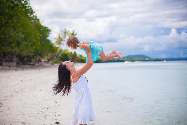 Junge mutter und ihre süße tochter haben spaß am exotischen strand Premium Fotos