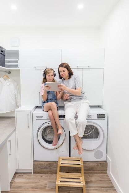Junge mutter und ihre tochter spielen mit tablette in der waschküche, die auf waschmaschine sitzt Premium Fotos