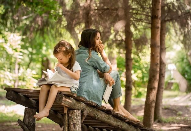 Junge mutter und tochter lasen im park auf einer holzbrücke ein buch, das konzept eines glücklichen familienlebens und familiärer beziehungen Kostenlose Fotos