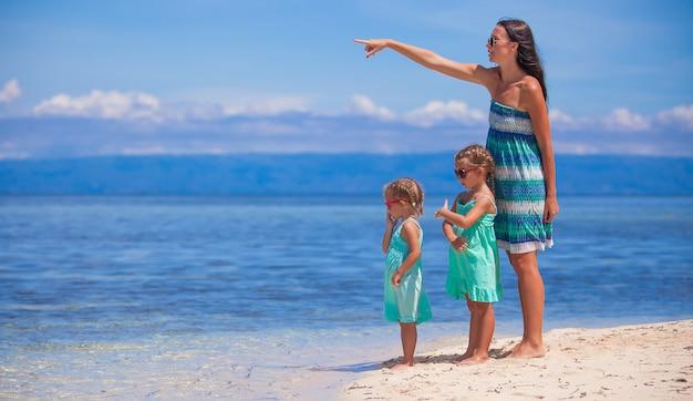 Junge mutter und zwei ihre töchter am exotischen strand am sonnigen tag Premium Fotos