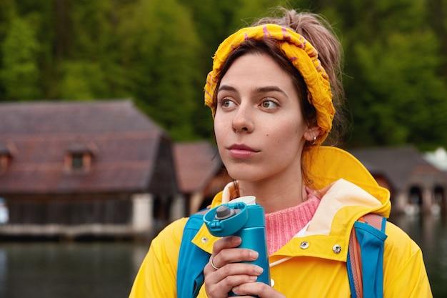 Junge nachdenkliche kaukasische frau trägt gelben schal und anorak Kostenlose Fotos