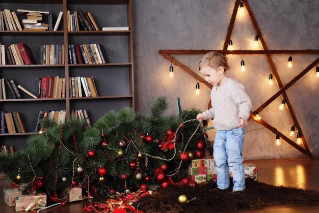 Junge nahe einem gefallenen weihnachtsbaum. weihnachtskonzept Premium Fotos