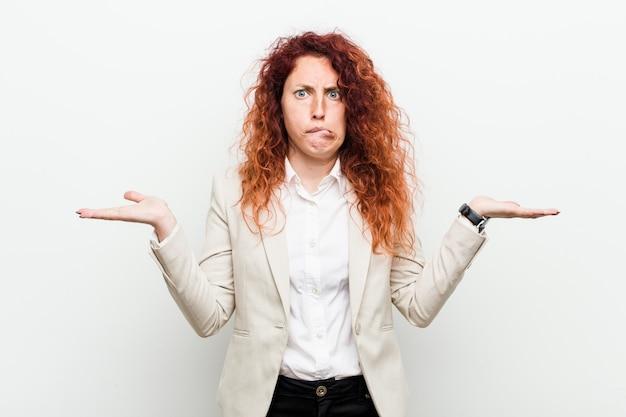 Junge natürliche rothaarigegeschäftsfrau lokalisiert gegen die weißen verwirrten und zweifelhaften achselzuckenschultern, um eine kopie zu halten. Premium Fotos