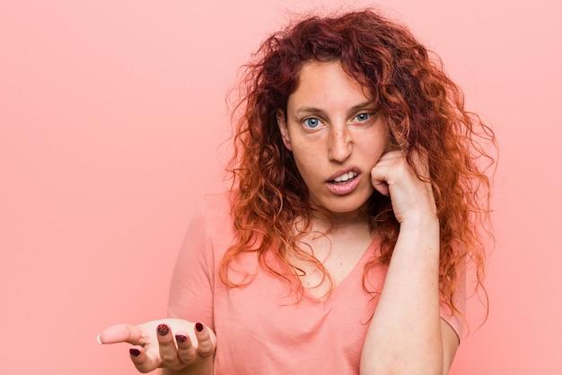 Junge natürliche und authentische rothaarigefrau, die eine enttäuschungsgeste mit dem zeigefinger zeigt. Premium Fotos