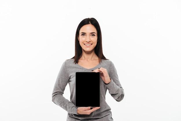 Junge nette dame, die anzeige des tablet-computers zeigt. Kostenlose Fotos