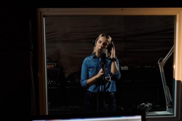 Junge nette hübsche lächelnde blondine, die ein lied notieren Premium Fotos
