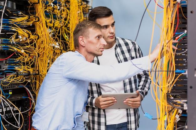 Junge netzingenieure, die in einem serverraum arbeiten Kostenlose Fotos