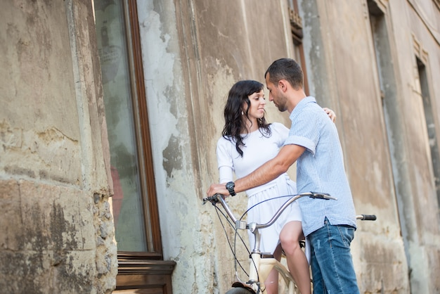 Junge paare auf retro- tandemfahrrad an der straßenstadt Premium Fotos