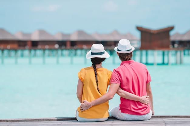 Junge paare auf strandanlegestelle in tropeninsel in den flitterwochen Premium Fotos